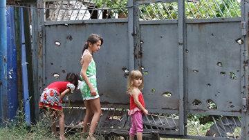 Дети у ворот, поврежденных осколками в результате обстрела украинских силовиков