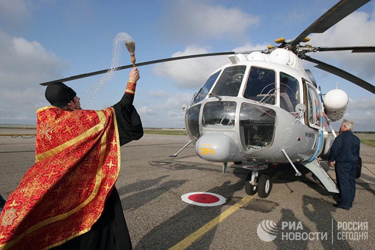 Священник Симферопольской и Крымской епархии Московского патриархата отец Василий освящает вертолет МИ-8 МЧС России