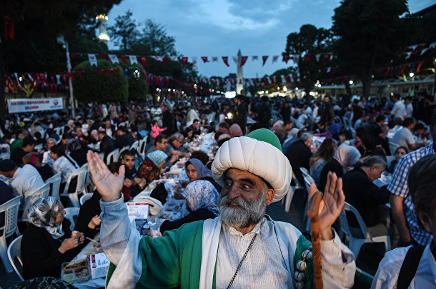 Мужчина в одежде в османском стиле радуется разговению мусульман в Голубой мечети Стамбула