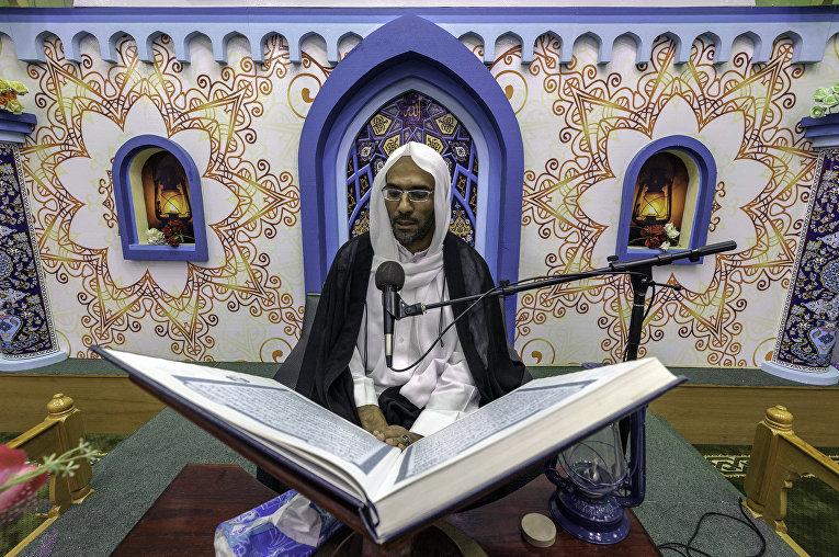 Саудовский религиозный деятель зачитывает копию Корана