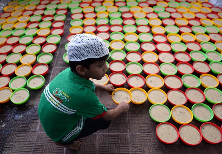 Индийский мальчик готовит длинные ряды тарелок с едой для Ифтара