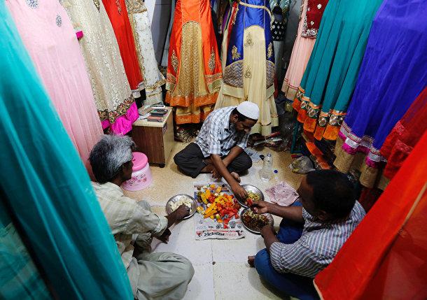 Продавцы вкушают ифтар в своем магазине одежды в Индии