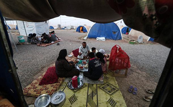 Семья вкушает ифтар в первый день Рамадана в лагере для временно перемещенных лиц