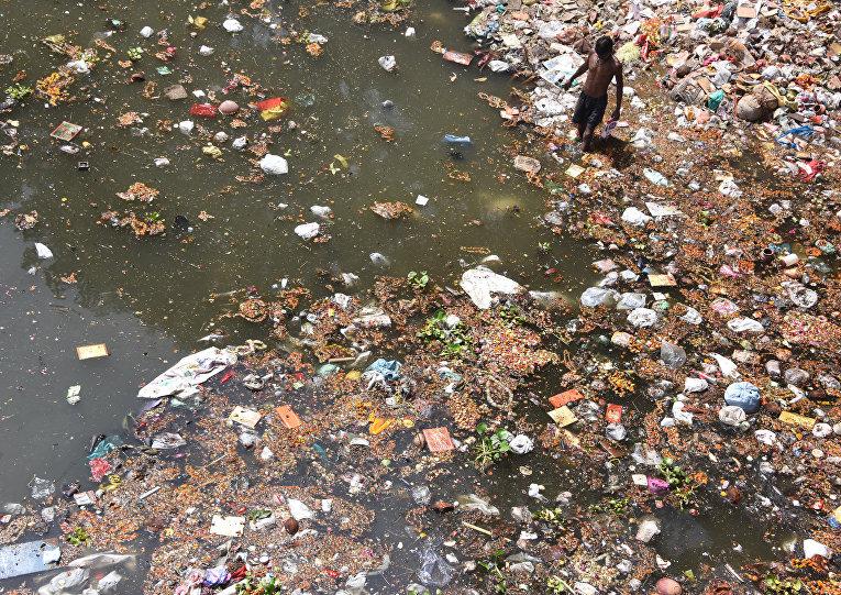 Индийский мусорщик в загрязненной реке Ямуна на окраине Нью-Дели