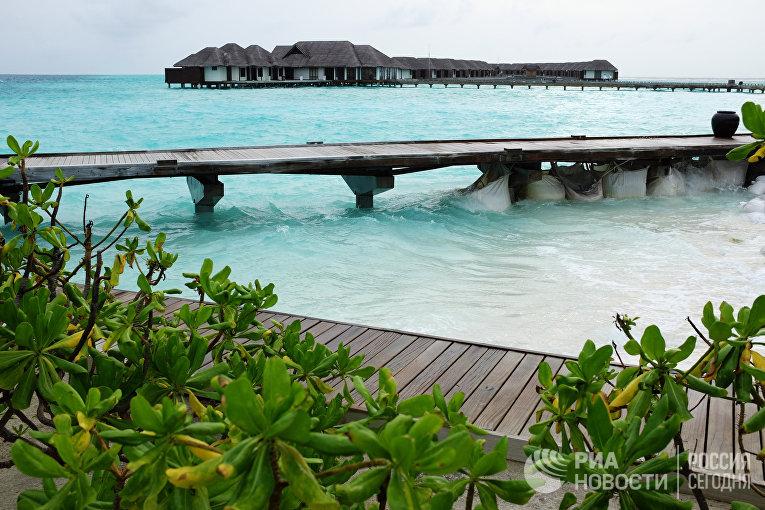 Виллы и мост на сваях в прибрежных водах острова Велассару (Мальдивы)