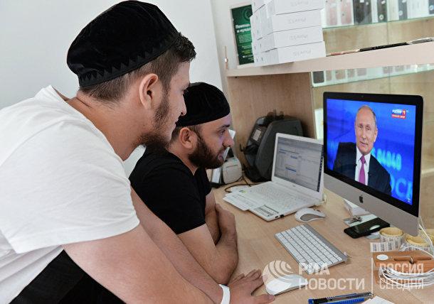 Мужчины смотрят трансляцию «Прямой линии с Владимиром Путиным» в Грозном