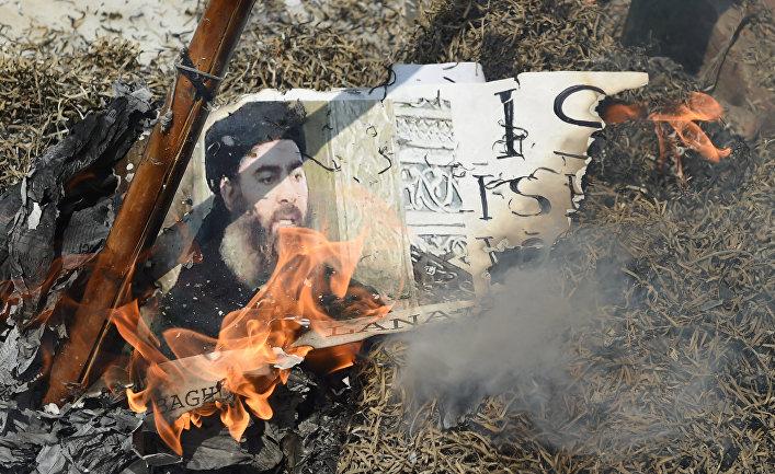 Горящая фотография лидера «Исламского государства» (запрещена в РФ) Абу Бакра аль-Багдади