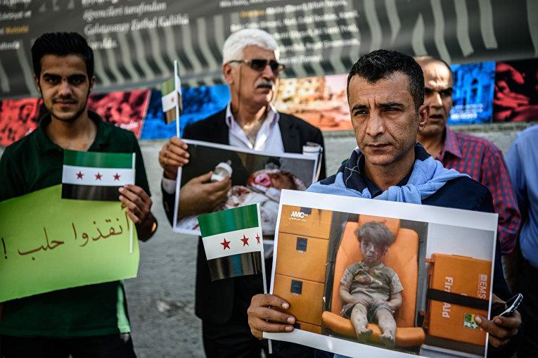 Сирийцы, живущие в Турции, с портретами мальчика Омрана, пострадавшего при обстреле Алеппо. 1 октября 2016