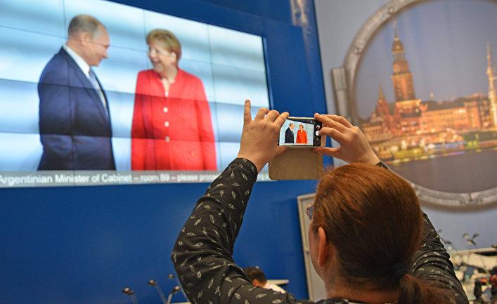 Журналисты в международном пресс-центре во время трансляции официальной встречи президента РФ Владимира Путина канцлером Германии Ангелой Меркель