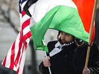 Ультраортодоксальный еврей антисионист с флагами США и Палестины во время акции протеста