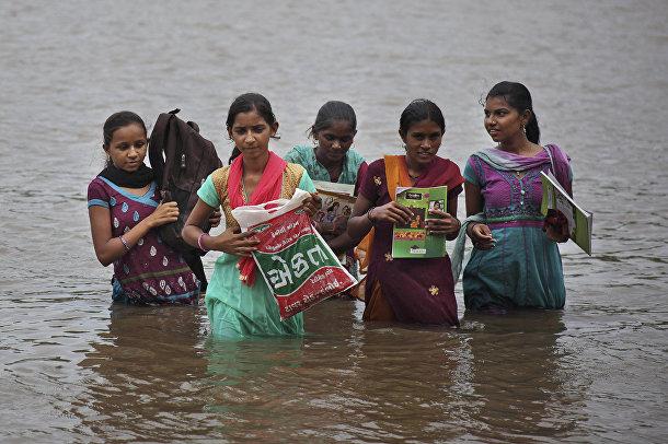 Индийские девочки пересекают реку Херана на пути из школы домой в деревне Севада в Индии