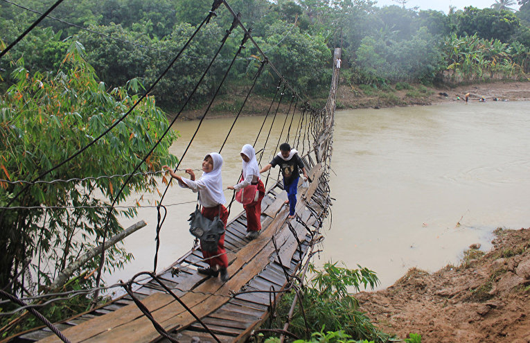 Дети из индонезийской деревни Сангьянг Танджунг по пути в школу