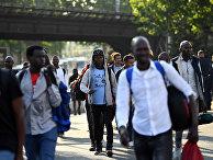 Беженцы во время эвакуации из импровизированного лагеря в Порт-де-ла-Шапель, на севере Парижа