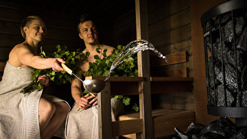 Женщина льет воду на камни в финской сауне