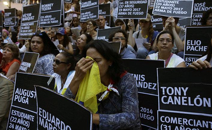 Демонстранты с именами пошибших во время антиправительственных протестов в Каракасе