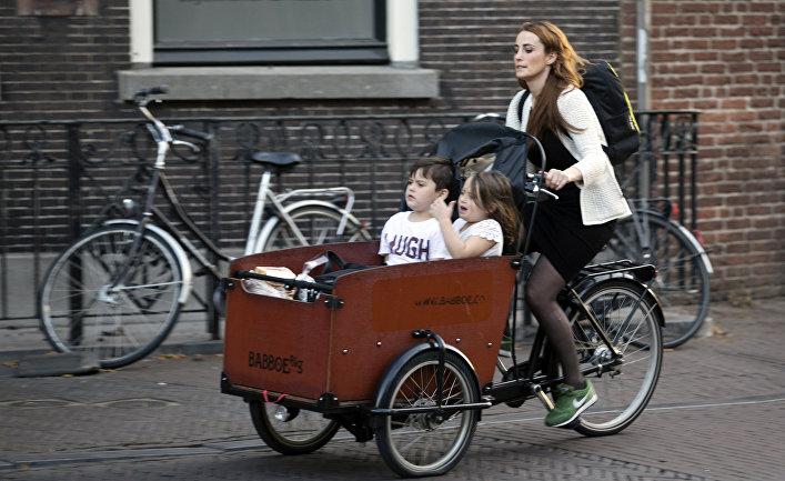 Женщина на велосипеде с детьми на одной из улиц Утрехта