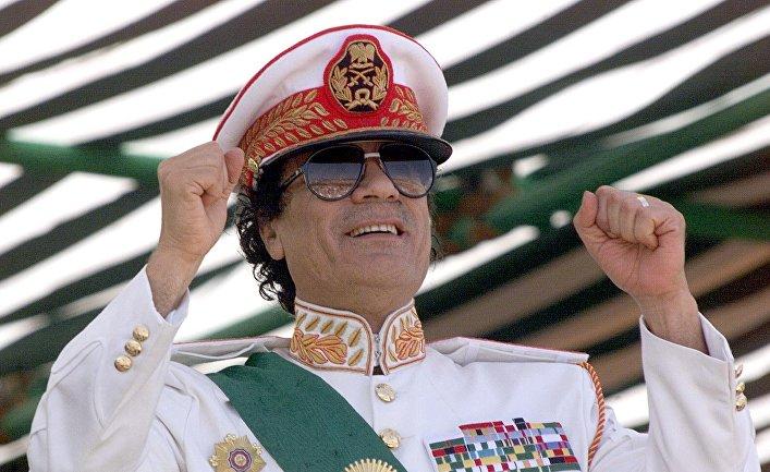 7 сентября 1999 года. Ливийский лидер Муаммар Каддафи приветствует своих солдат во время военного парада в Трипло