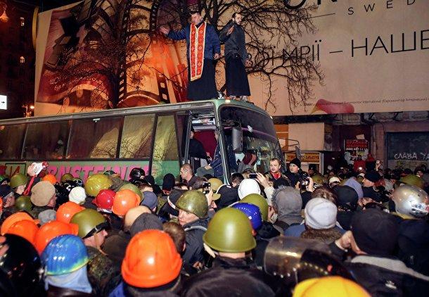Священники стоят на автобусе во время демонстраций в Киеве