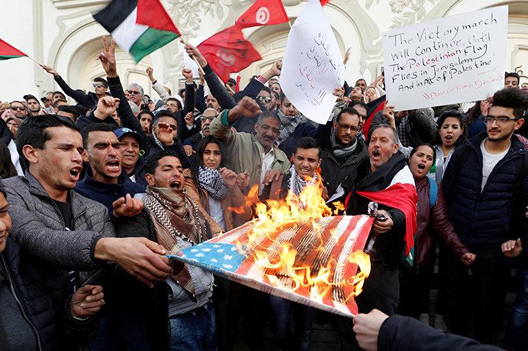 Протестующие сжигают флаг США во время протеста против решения Дональда Трампа признать Иерусалим столицей Израиля в Тунисе. 7 декабря 2017