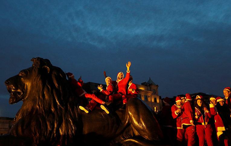 Люди во время фестиваля Санта-Клаусов на Трафальгарской площади в Лондоне