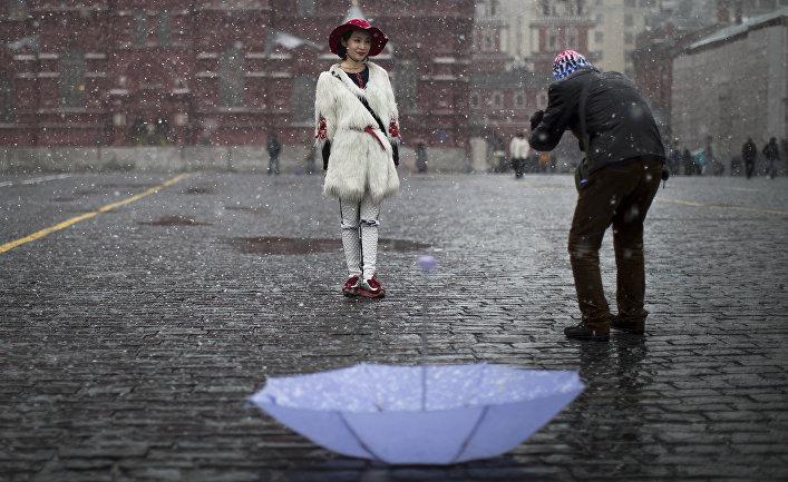 Китайские туристы фотографируются на Красной площади во время снегопада