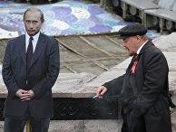 Двойник создателя Советского государства В.И.Ленина курит рядом с фотографией президента РФ Владимира Путина
