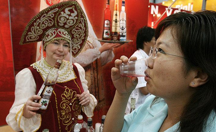 Женщина пробует ягодную водку на выставке российских продуктов в Шанхае