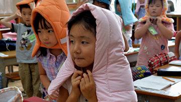 Дети начальной школы в Токио в огнеупорных капюшонах