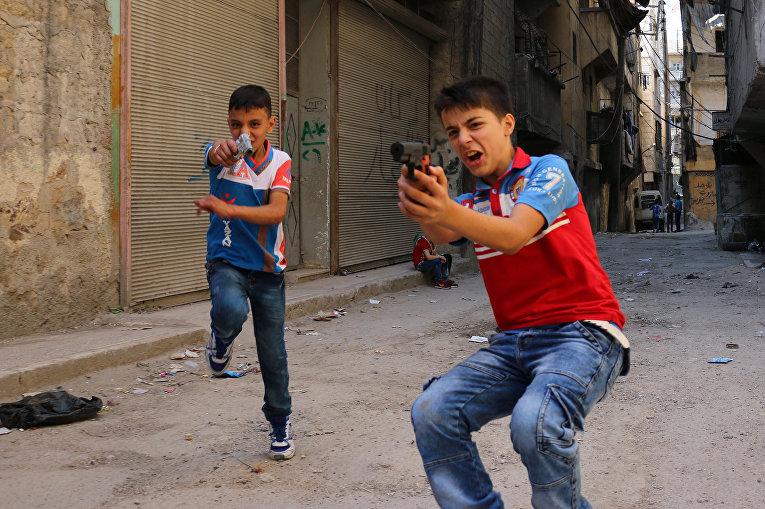 Сирийские дети играют на улице с игрушечным оружием в Алеппо