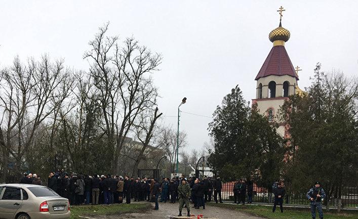 Жители несут цветы к Свято-Георгиевскому храму в Кизляре