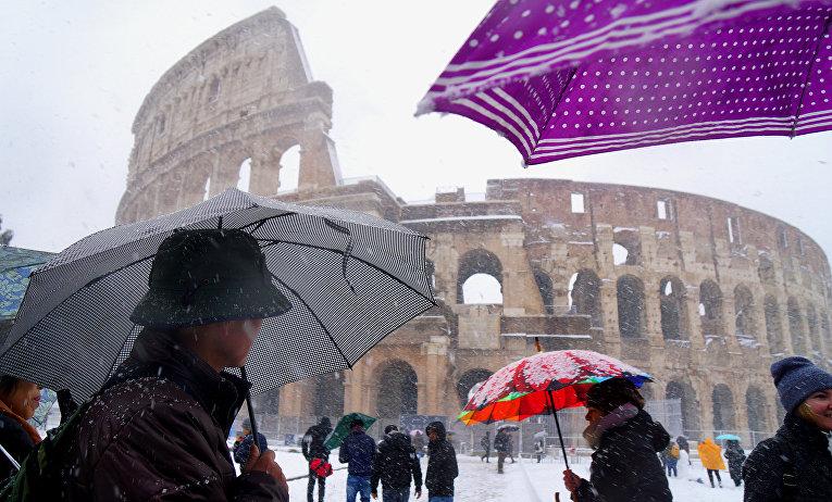 Люди с зонтами перед Колизеем во время снегопада в Риме, Италия