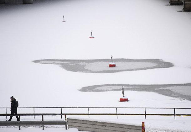 Мужчина идет мимо замерзших вод Стокгольмского порта, Стокгольм, Швеция
