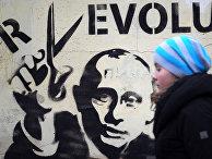 Девушка идет мимо стены с граффити с изображением Владимира Путина.