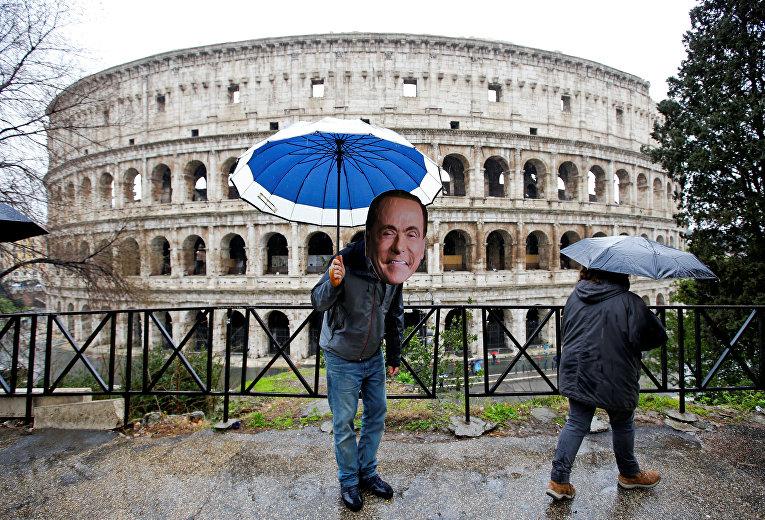 """Активист в маске лидера партии """"Вперед, Италия"""" Сильвио Берлускони на следующий день после парламентских выборов в Риме"""