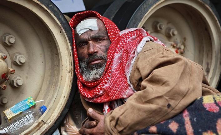 Мужчина сидит у гусениц танка. Оппозиционеры на площади Тахрир в Каире блокировали военную технику, не давая ей передвигаться по площади