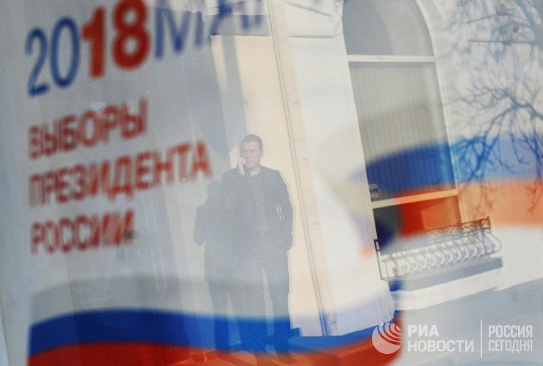 Отражение в окне баннера с информацией о выборах президента России 18 марта 2018.