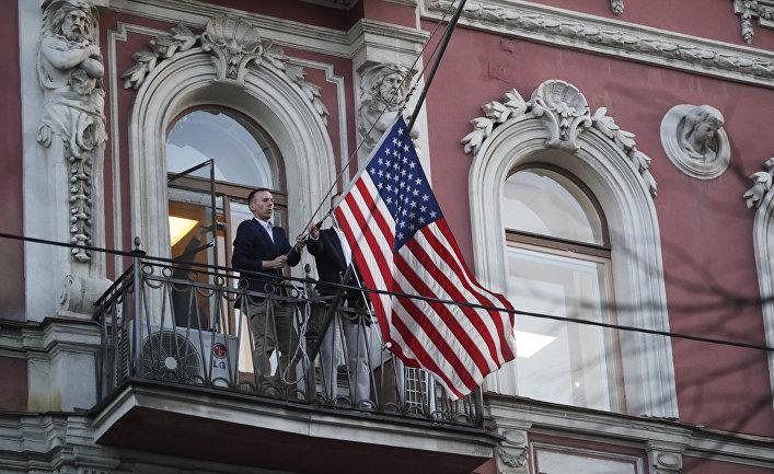 Сотрудники дипмиссии снимают государственный флаг США со здания американского генконсульства в Санкт-Петербурге
