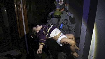 Спасатель несет ребенка после химической атаки в Думе, Сирия