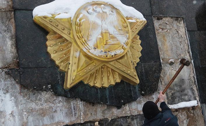 Националист сбивает облицовку на Монументе Славы во Львове