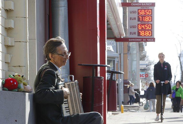 Уличный музыкант в Москве играет недалеко от вывески с курсом обмена валют