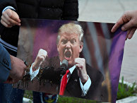 Участники акции протеста сжигают портрет президента США Дональда Трампа