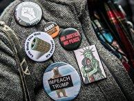 Значки на пальто одного из участников акции протеста против ударов по Сирии в Нью-Йорке