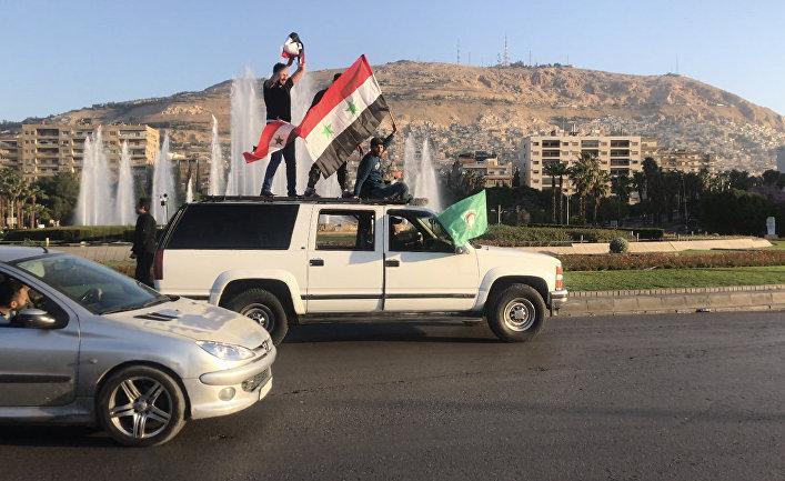 Жители на одной из улиц в Дамаске. 14 апреля 2018