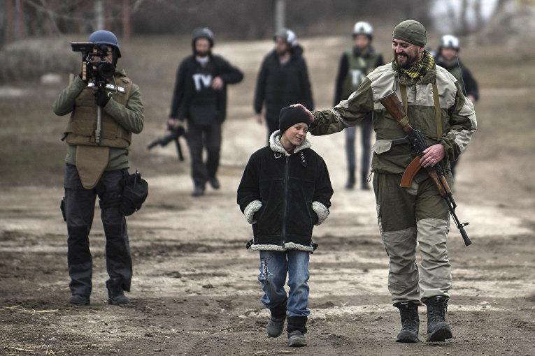 Украинский военный общается со школьником в селе Чермалык на востоке Украины