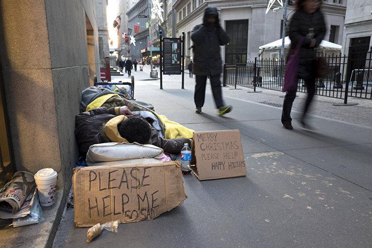 Бездомный спит на Уолл-стрит возле нью-йоркской фондовой биржи