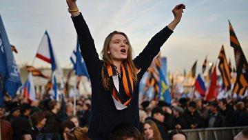 Участники митинга-концерта, посвященного годовщине воссоединения Крыма с Россией, на Васильевском спуске Москвы