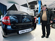 "Мужчина выбирает автомобиль ""Лада Гранта"" в автосалоне"