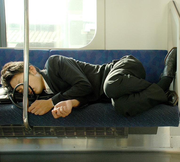 Мужчина спит в вагоне метро Токио