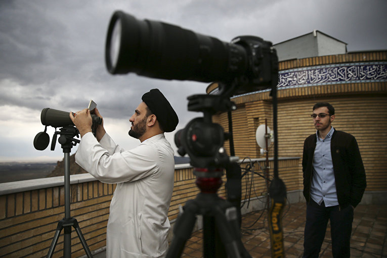 Иранский священнослужитель Мохаммад Хоссейн Дехсорхи наблюдает за луной в бинокль