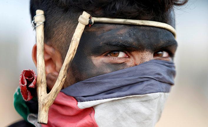 Палестинский демонстрант во время столкновений с израильскими войсками в Газе. 14 мая 2018